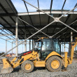 Wheeled tractor on modern storehouse construction site — Stock Photo