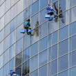 Window washers on a highrise office building in downtown - Stock Photo