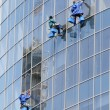 Stock Photo: Three window washers on highrise office building