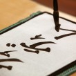 Close up of male hand writing Japanese characters — Stock Photo