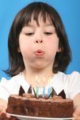 Happy girl blowing on birthday cake (studio shot) — Stock Photo