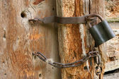 Padlock and chain on an old door — Stock Photo