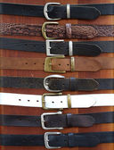 Leather belts on wood background — Stock Photo