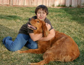 Happy teenage boy with big red dog — Stock Photo