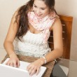 Stock Photo: Young student using her laptop at home