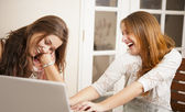 Two young women having fun in front of laptop — Stock Photo
