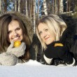 Royalty-Free Stock Photo: Two girls eat a pear in the snow