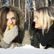 Stock Photo: Two girls in snow eat pear and jealous