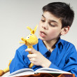 Boy reading a book with a toy in the background — Stock Photo
