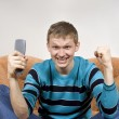The guy shouts happily, watching tv — Stock Photo