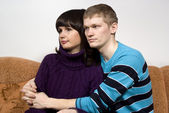 The guy hugging a girl, sitting on the couch — Stock Photo