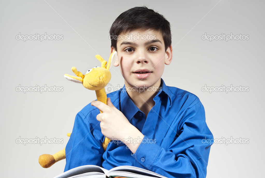 Boy with a book and toy in the background — Stock Photo #10092353