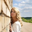 Beautiful girl near the wall - Stock Photo
