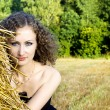 Beautiful curly girl near the sheaf of hay in nature - Stock Photo