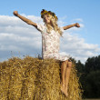 Beautiful girl blonde sitting on hay — Stockfoto #10249818