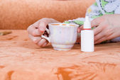 Cup of tea and a nasal spray — Stok fotoğraf