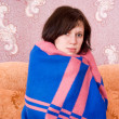 Girl fell ill and wrapped in a blanket on the couch — Stock Photo #10250049