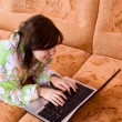 Girl in a bathrobe running a laptop on the couch — Stock Photo