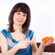 Girl sitting on the bed and keeps mandarins — Stock Photo
