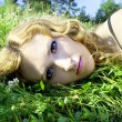 Stock Photo: On nature of beautiful red-haired girl in grass