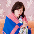 Royalty-Free Stock Photo: Sick girl on the couch with a thermometer