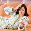 The girl fell ill and measures the temperature on the couch - ストック写真