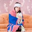 Thermometer girl in a bathrobe on the couch - ストック写真