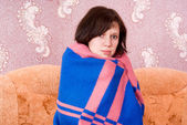 Girl fell ill and wrapped in a blanket on the couch — Stok fotoğraf