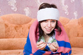 Girl lying on the couch sick with a thermometer — Stock Photo