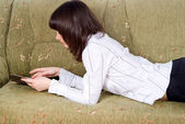 Girl reading a book on the couch — Stock Photo