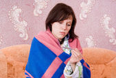 Sick girl on the couch with a thermometer — Stock Photo
