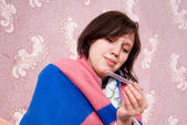 Sick girl thermometer in a bathrobe — Stock Photo