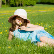 A young girl was lying in a meadow, and holds a flower — Stock Photo
