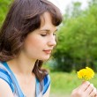 Beautiful girl looking at the flowers, in nature — Stock Photo