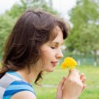 Beautiful girl sniff dandelion, in nature — Stock Photo