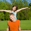 The father holds the daughter on her back, in nature — Stock Photo