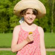 The girl in a hat holding a flower, in nature — Stock Photo