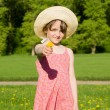 The girl in the hat offers a flower, in nature — Stock Photo