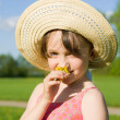 The girl in the hat smelling a flower, in nature — Stock Photo