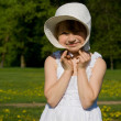 The girl on meadow, holds the hat — Stock Photo