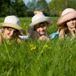 Stock Photo: Three girls lie in grass, in nature