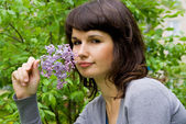 Beautiful girl keeps lilac, in nature — Stock Photo