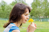 Beautiful girl sniff dandelion, in nature — Stock Photo