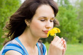 Beautiful girl sniff the flowers, in nature — Stock Photo
