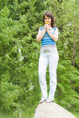 Beautiful girl standing on a rock, in nature — Stock Photo