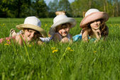 Three girls lie in the grass, in nature — Stock Photo