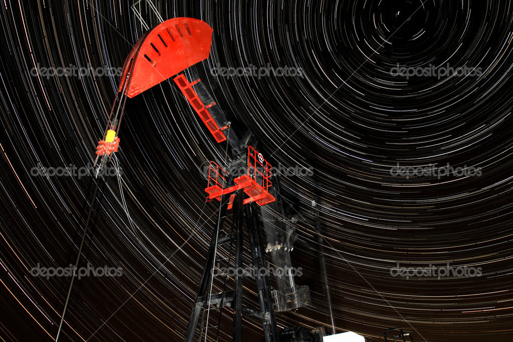 An orange and black pump jack with star trails in the background.  Stock Photo #9605676