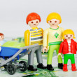 Child allowance - Playmobil Family and 100 euro banknotes - Stock Photo