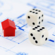 Red model house with architecture plan and dices - Stock Photo