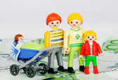 Child allowance - Playmobil Family and 100 euro banknotes — Stok fotoğraf